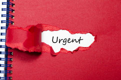 The word urgent appearing behind torn paper Royalty Free Stock Image