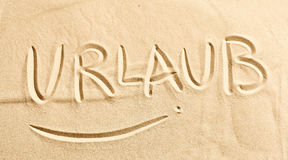 The word Urlaub written in golden beach sand Royalty Free Stock Photography