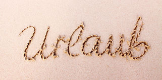Word  Urlaub written in sand. Royalty Free Stock Photo