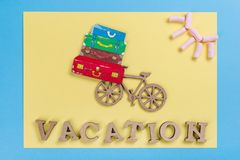Word vacation abstract wooden letters. Background blue yellow, image of heap of suitcases on bicycle Stock Photo