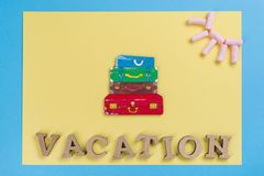 Word vacation abstract wooden letters. Background blue yellow, image of heap of suitcases Royalty Free Stock Photos