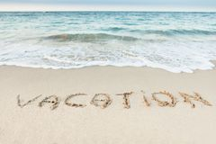 Word vacation written on beach Stock Images