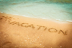 The word vacation written in the sand on a beach Royalty Free Stock Images