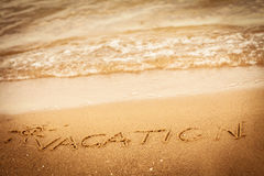 The word vacation written in the sand on a beach Stock Images