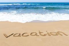 Word vacation written on sandy beach near sea Stock Image