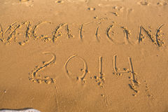 Word vacation on the yellow sandy beach Royalty Free Stock Image