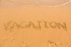 Word vacation on the yellow sandy beach Royalty Free Stock Photos