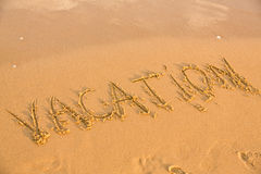 Word vacation on the yellow sandy beach Royalty Free Stock Photo