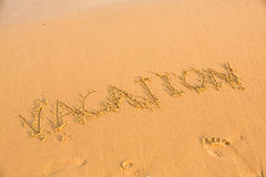 Word vacation on the yellow sandy beach Royalty Free Stock Images