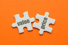 The word Value Price on two matching puzzle on orange background.  Royalty Free Stock Photos