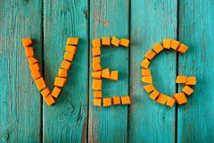 Word Veg written with raw pumpkin pieces on wooden turquoise tab Stock Images