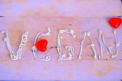 Word vegan with two red heart stock photography