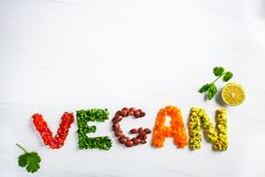 The word vegan on white background, top view. Vegan food concept. Vegan composed of beans, guacamole, vegetables and herbs