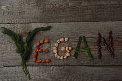 The word vegan written plant foods: beans,dill,  nuts, cucumber. go vegan Royalty Free Stock Photography