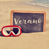 Word verano, summer in spanish, in a chalkboard on the beach Stock Photos