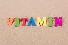 Word vitamine D van gekleurde houten brieven op zandig strand stock foto's