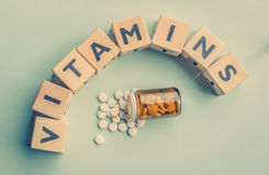 The word vitamins on a table. With a glass of pills Stock Images