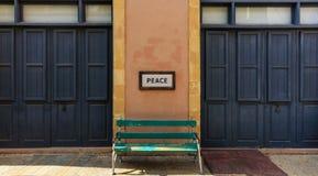 Word vrede boven een oude houten bank op een kolom tussen twee deuren wordt ontworpen die Sluit omhoog mening royalty-vrije stock fotografie