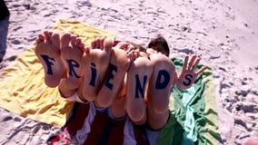 Word vrienden op de voeten jonge vrouwen die bij het strand liggen stock video