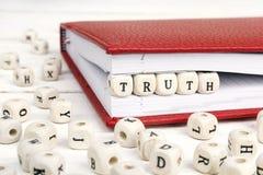 Word Waarheid in houten blokken in rood notitieboekje op witte wo wordt geschreven die Stock Foto's