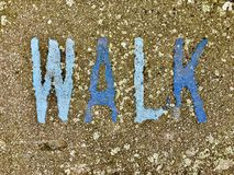 The word WALK on the floor in a kids park. The word WALK stencilled in baby and navy letters onto the floor made out of wet pour rubber surface material in a stock photography