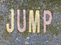The word JUMP on the floor in a kids park. The word WALK stencilled in baby and navy letters onto the floor made out of wet pour rubber surface material in a royalty free stock photography
