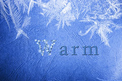 Word warm written on winter snowy blue background. Royalty Free Stock Photos