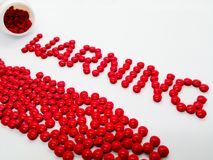 Word warning made from red tablets, isolated on white background royalty free stock photography