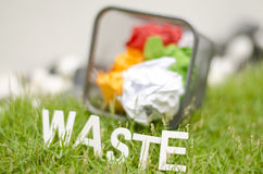 Word waste made from wood in arc position placed on green grass. Royalty Free Stock Photography