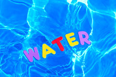 Word WATER floating in a swimming pool Royalty Free Stock Images