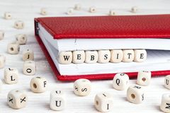 Word Website written in wooden blocks in red notebook on white w royalty free stock photography