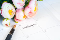 Word wedding on calendar with sweet flowers and pen Royalty Free Stock Image