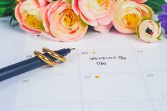 Word Wedding to Reminder Wedding day with Wedding ring on calendar planning. And office tool stock photography