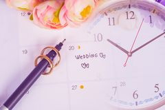 Word Wedding to Reminder Wedding day with Wedding ring on calendar planning. And clock stock photos