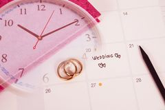 Word Wedding to Reminder Wedding day with Wedding ring on calendar planning. And clock stock images