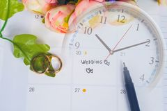 Word Wedding to Reminder Wedding day with Wedding ring on calendar planning. And clock royalty free stock images