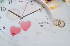 Word Wedding to Reminder Wedding day with Wedding ring on calendar planning. And clock royalty free stock image