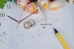 Word Wedding to Reminder Wedding day with Wedding ring on calendar planning. And clock stock image