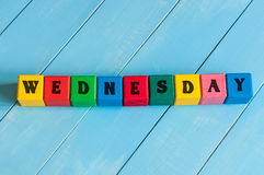 The word Wednesday written in child's color wooden. Cubes, on light blue wood background stock photography