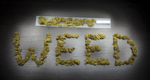 Word Weed written with cannabis dried plant. On a black wooden table. Rolling paper with filter and marijuana stock image