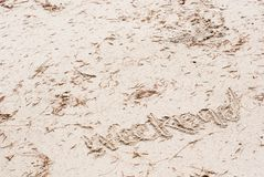 The word `weekend` is written on beach sand with brown pine leaves on it suit for holiday atmosphere stock image