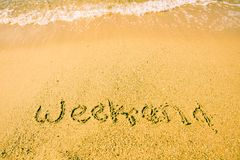 Word Weekend written on sand. Sandy beach with word Weekend written on sand. leisure time concept royalty free stock images