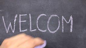 Word WELCOM wordt geschreven in krijt op een bord stock video