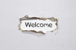 The word welcome appearing behind torn paper. The word welcome appearing behind torn paper Stock Photos