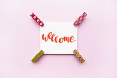 Word Welcome handwritten with watercolor in calligraphy style, miniature clothespins on a pink background. Flat lay Royalty Free Stock Photos
