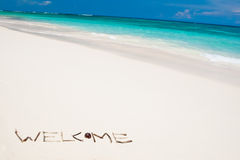 Word welcome on a white sand beach near blue ocean Stock Photos