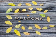Word Welcome on a wooden background, frame of yellow leaves Royalty Free Stock Photography
