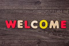 Word Welcome from wooden letters. On dark wooden background Stock Image