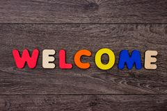 Word Welcome from wooden letters. On dark wooden background Royalty Free Stock Photo