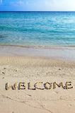 Word welcome   is written on sand on oceanside Stock Photo